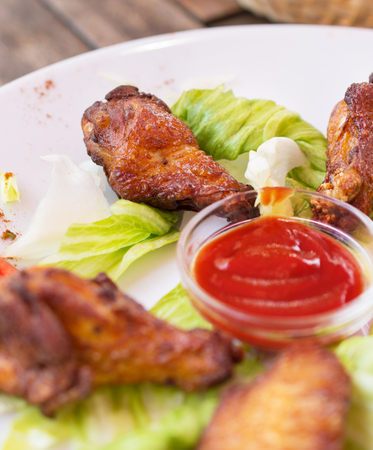 Grilled chicken wings with ketchup and greens  Closeup photo  photo