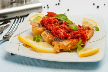 Pieces of fried fish in tomato marinade  With lemon and herbs  Stock Photo