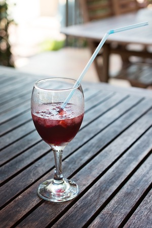 punch: A glass half-full glass of sangria and ice  With plastic pipe  Stock Photo