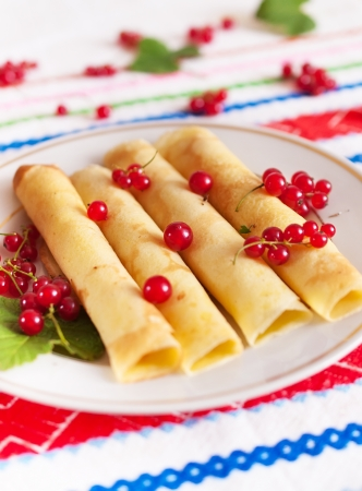 Pancakes rolled into a tube and decorated with red currant berries  Stock Photo