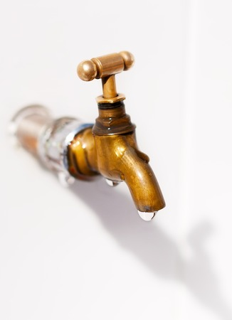 Brass faucet  As the drops of water  On a white background Фото со стока - 23217493