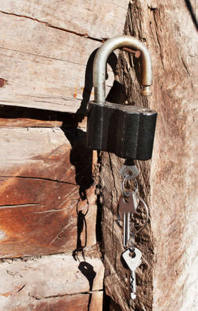 Padlock with keys on a wooden wall on the background  photo