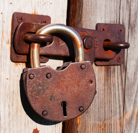 Old rusty padlock on a wooden door photo
