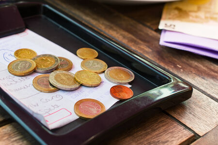tipping: Euro coins on cash receipt from the restaurant