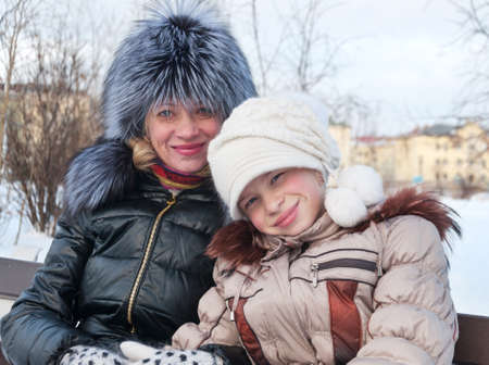 Mom and daughter in a winter park  In winter clothes  photo
