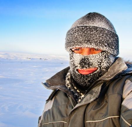 Retrato de un hombre con una gorra y una máscara de esquí de invierno en las heladas Foto de archivo - 25241449
