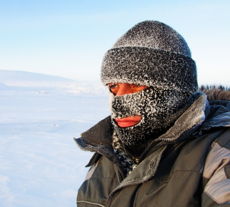 Portrait of a man in a cap and a ski mask  Winter in frost  版權商用圖片