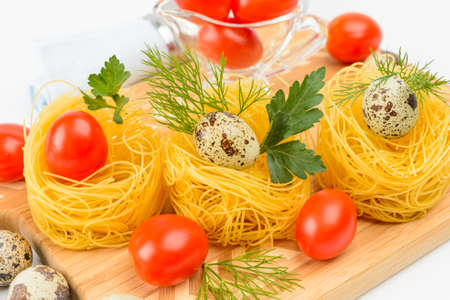 Italian pasta nests with cherry tomatoes and quail eggs  photo
