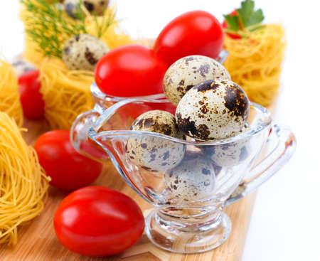 Glass Gravy boat with quail eggs  On the background of pasta nests and cherry tomatoes  photo