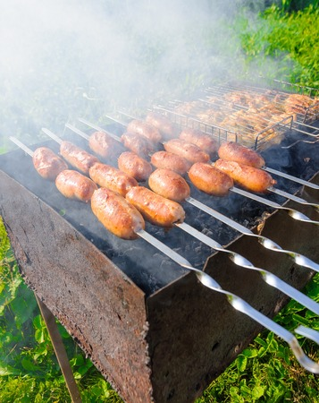 brazier: Cooking sausages on skewers in the brazier