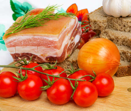 Salty piece of lard with cherry tomatoes and garlic  photo