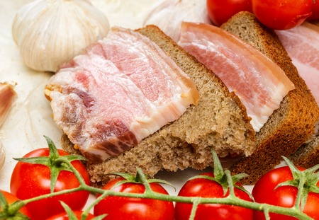Of salted bacon sandwiches on rye bread  With cherry tomatoes and garlic  photo