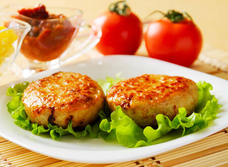 chicken meat: Two chicken cutlets on the green leaf lettuce  Decorated with fresh vegetables