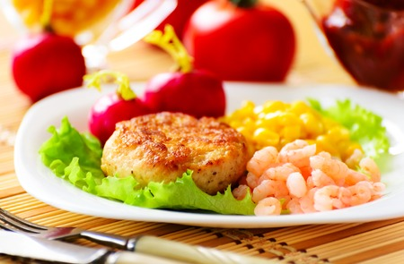 Chicken cutlets with canned corn and peeled shrimp  Served with fresh vegetables  photo