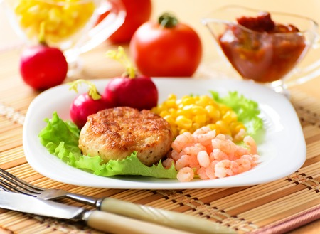 Chicken cutlets with canned corn and peeled shrimp  Served with fresh vegetables and radih  photo