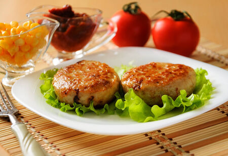 Two chicken cutlets on the green leaf lettuce  Decorated with fresh vegetables  photo