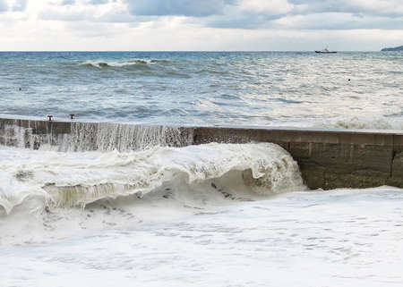 Storm waves roll on the concrete breakwater