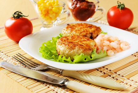 Meat chops in the plate with the peeled shrimp  photo