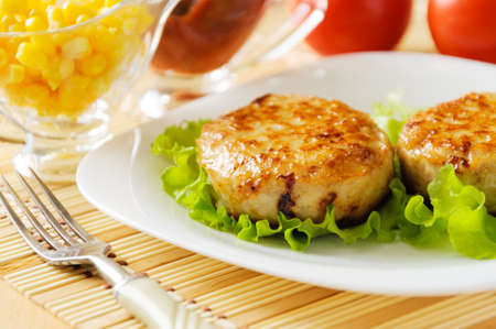Meat patties on a white plate  Served with fresh vegetables  photo
