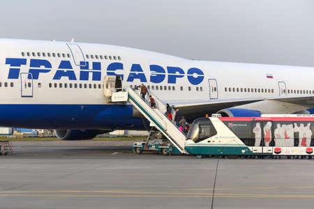 boeing 747: MOSCA, RUSSIA - 26 settembre 2014: I passeggeri salire la scala nel piano compagnie aeree Boeing 747 Transaero. Transaero Airlines ha cessato di esistere nel 2015.