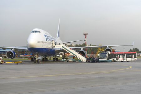 boeing 747: MOSCOW, RUSSIA - SEPTEMBER 26, 2014: Passengers climb the ladder into the plane Boeing 747 Transaero airlines. Transaero Airlines has ceased to exist in 2015.