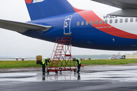 azur: MOSCOW, RUSSIA - MAY 19, 2016: Service engineers mounted the stairs near airplane Azur Air Airline Boeing 757-200.