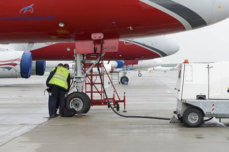 carry out: MOSCOW, RUSSIA - MAY 19, 2016: Aircraft  Tupolev-204 Red Wings airline in the parking lot of the international airport Domodedovo. The service engineer carry out work on inspection of the landing gear.