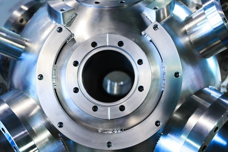 flanges: Industrial background, heavy metal housing with welded metal flanges. Stock Photo
