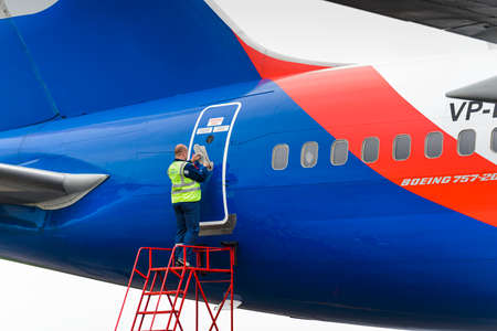 azur: MOSCOW, RUSSIA - MAY 19, 2016: Service engineer opens the plane door Azur Air Airline Boeing 757-200.