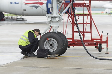 out of work: MOSCOW, RUSSIA - MAY 19, 2016: Aircraft  Tupolev-204 Red Wings airline in the parking lot of the international airport Domodedovo. The service engineer carry out work on inspection of the landing gear.