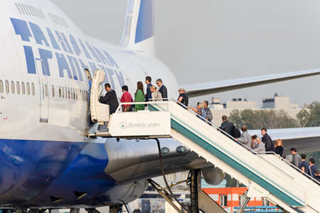 ceased: MOSCOW, RUSSIA - SEPTEMBER 26, 2014: Passengers climb the ladder into the plane Boeing 747 Transaero airlines. Transaero Airlines has ceased to exist in 2015.