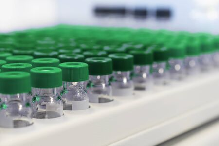 plactic: Rows of glass vials in the tray automatic liquid dispenser. Laboratory chemical equipments. Small glkbina field.