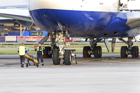 ceased: MOSCOW, RUSSIA - SEPTEMBER 26, 2014: Experts airfield services Domodedovo airport preparing to tow the aircraft. Transaero Airlines has ceased to exist in 2015.