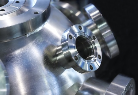 shiny metal: Flanged vacuum equipment. Shiny metal surface. A metal surface treated. Focus on a metal casing.
