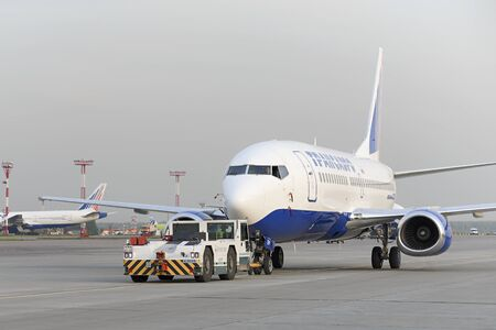 towed: MOSCOW, RUSSIA - SEPTEMBER 26, 2014: Boeing 737 Transaero towed tractor maintenance Transaero Airlines has ceased to exist in 2015.