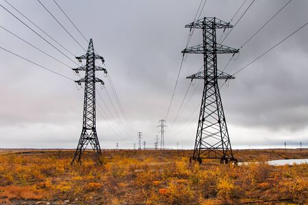 Supports high-voltage line. The tundra in the Arctic Circle, deep autumn. Cloudy day, bad lighting conditions.
