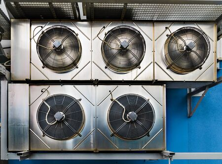 chiller: Industrial air conditioning units. Five cooling modules hang on the wall of a building.