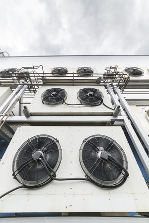 plurality: Industrial air conditioning units. A plurality of cooling units installed in the wall of a building. Stock Photo