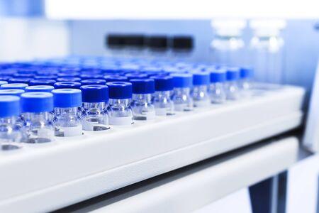 Las filas de viales de vidrio en el dispensador automático de líquidos bandeja. equipos químicos de laboratorio. Poca profundidad de campo Foto de archivo - 61351298