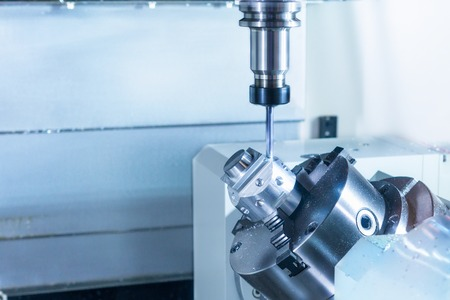 automated tooling: CNC milling machine during operation. Produce drill holes in the metal part. Stock Photo