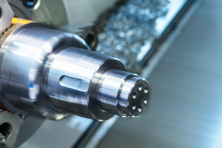 workpiece: A metal workpiece clamped in the lathe chuck CNC machine. Shallow depth of field.