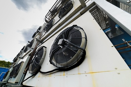 Cooling industrial air conditioning unit. Mounted on the wall of the building.