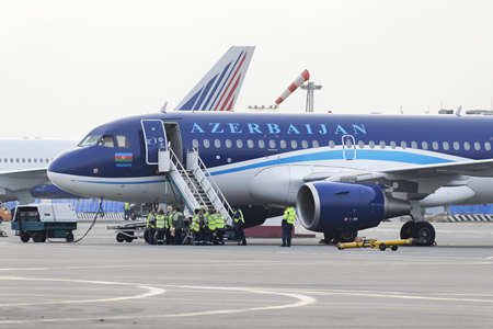 cleaning team: MOSCOW, RUSSIA - SEPTEMBER 26, 2014:  Airbus A320 Azerbaijan Airlines on the apron of Domodedovo Airport expects passenger compartment cleaning team. Editorial