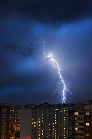 thundershower: Storm clouds, heavy rain. Thunderstorm and lightning over the night city. Stock Photo