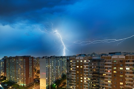 Storm clouds, heavy rain. Thunderstorm and lightning over the night city. Stock Photo