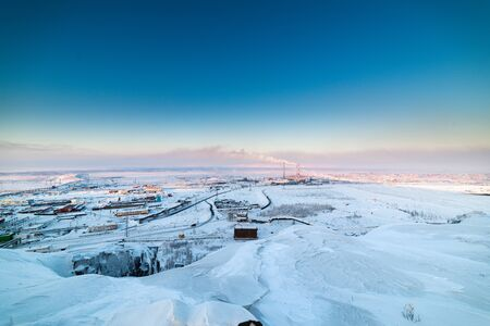 Industrial site metallurgical plant in the Arctic tundra. Grey polar twilight, a low setting sun. Stock Photo
