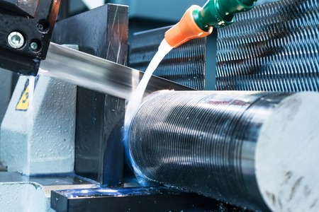 Automatic bandsaw sawing metal workpiece. From the cooling pipes supplied lubricity emulsion. Stockfoto