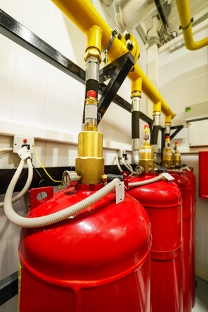 Cylinders and pipe fittings of industrial extinguishing system. Standard-Bild