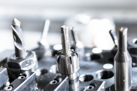 sharpening process: Cutters for metal and drill set the CNC machine tool magazine. Metal shavings.