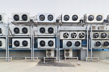 chiller: Industrial air conditioning units. A plurality of cooling units installed in the wall of a building. Stock Photo